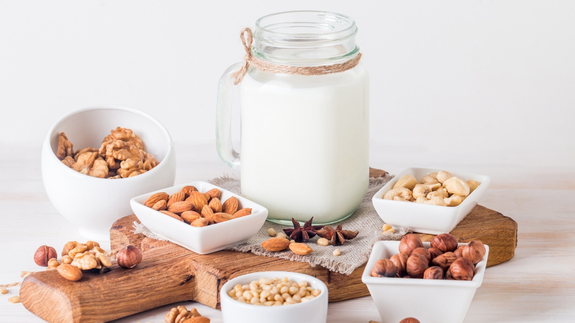 Nut milk in a bottle with many nuts around