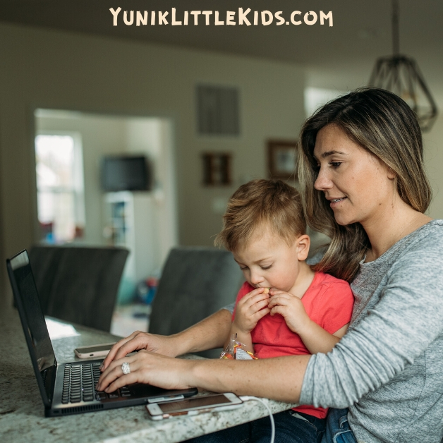 Mom working on laptop with kid